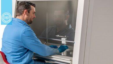 یک مرد در حال کار با هود بیولوژیکی